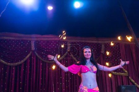 Photo pour Danseur de feu féminin aux cheveux foncés exotiques portant le rose lumineux et le costume orange twirling deux apparatus flamboyant de bâton sur l'étape avec le rideau rouge et le rétroéclairé par les projecteurs lumineux - image libre de droit