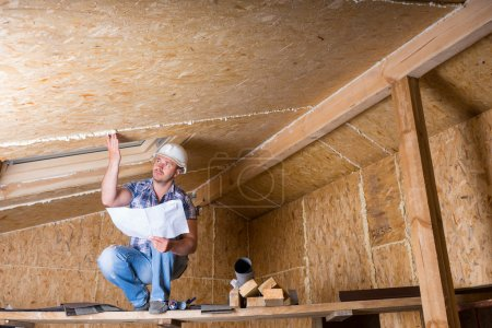 Male Construction Worker Builder Wearing White Hard Hat Crouching on Elevated Scaffolding and Reading Plans near Ceiling of Unfinished Home with Exposed Plywood Particle Board