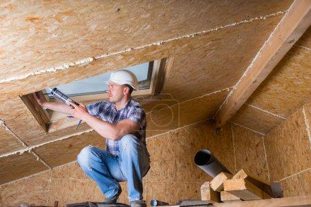Construction Worker Applying Caulking to Sky Light