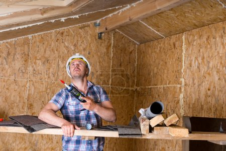 Builder with Caulking Gun Inside Unfinished Home