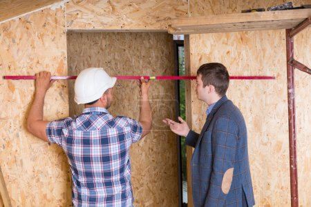 Builder and Architect Inspecting Door Frame