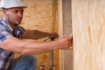 Ouvrier, mesurer la largeur du cadre de porte