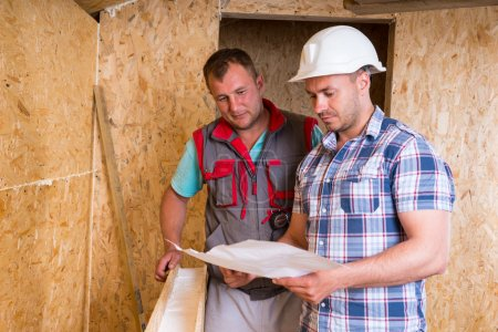 Construction Workers Consulting Plans in New Home