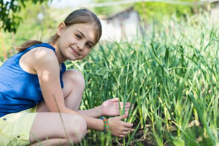 Smiling young girl checking onion plants
