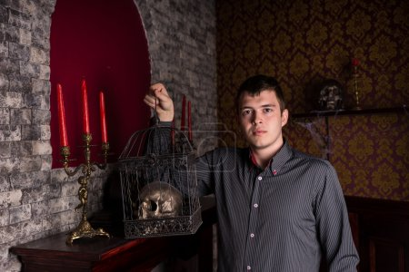 Young Man Holding Skull in Cage Inside Castle