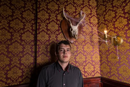 Young Man Posing Beneath Antlered Deer Skull