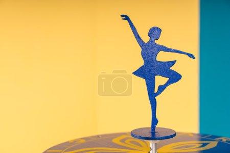 Photo pour Statue gracieuse de silhouette de danseuse de ballerine sur la table dans la salle avec les murs jaunes et bleus colorés avec l'espace de copie - image libre de droit