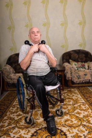 Photo pour Portrait complet de l'homme aîné avec la jambe amputée s'asseyant dans le fauteuil roulant retenant des haltères portatifs dans le confort de la maison dans la salle de séjour - image libre de droit