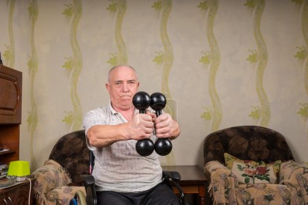 Senior Man in Wheelchair Lifting Dumbbells at Home