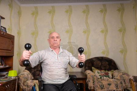 Invalid old man doing exercises with dumbbells