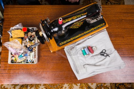 Old Fashioned Sewing Machine and Supplies on Table