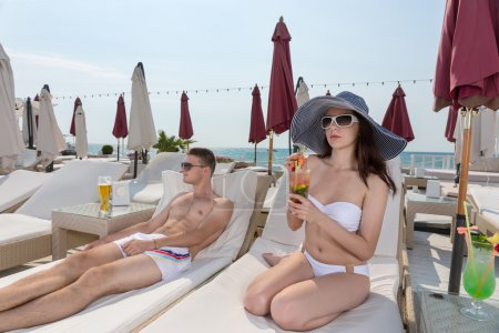 Young Couple Relaxing on Deck of Beach Resort