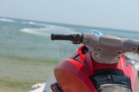 Red jet ski in shallow water off the beach
