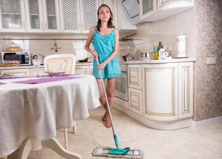 Young Woman Daydreaming and Mopping Kitchen Floor