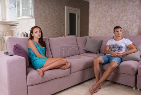 Couple Sitting Apart on Sofa in Living Room