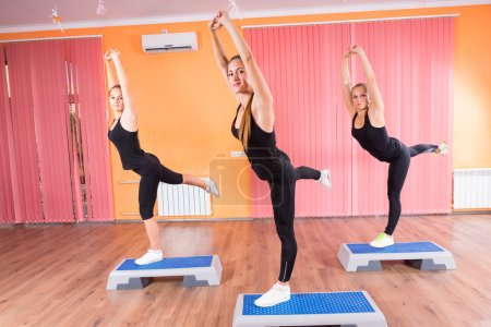 Girls Stretching and Balancing on Aerobic Steps