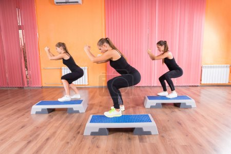 Photo for Three Healthy Women Doing Squatting Exercise Simultaneously Using Aerobic Step Platforms Inside the Gym. - Royalty Free Image
