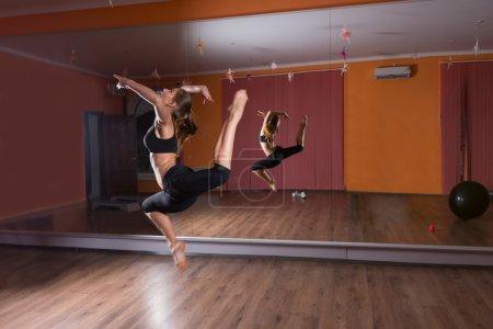 Female Dancer Leaping in Air in Dance Studio
