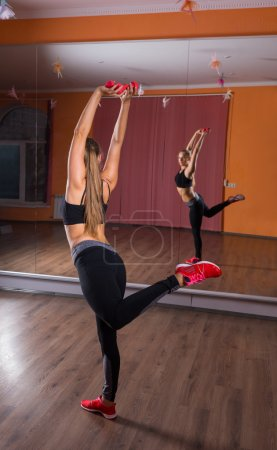 Young Woman Balancing on One Leg in Dance Studio