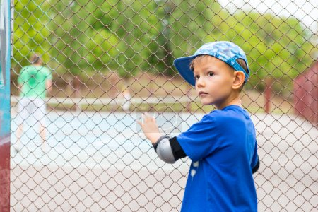 Small boy watching a game of tennis