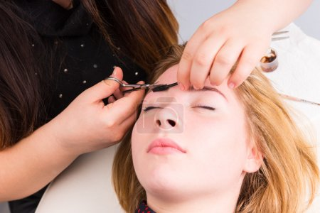 Woman Having Eyebrows Trimmed by Esthetician
