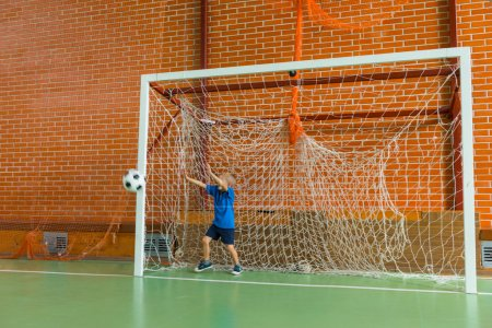 Young soccer goalkeeper practicing indoors