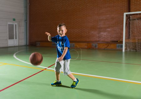 Laughing young boy playing basketball