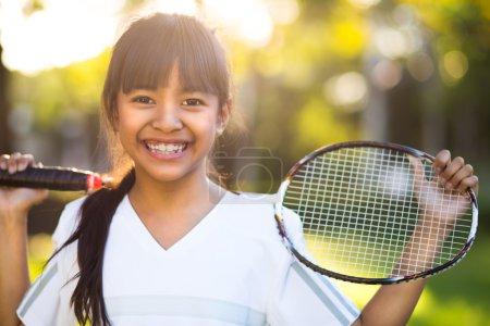 Photo pour Gros plan mignonne petite fille asiatique tenant une raquette de badminton, Extérieur - image libre de droit