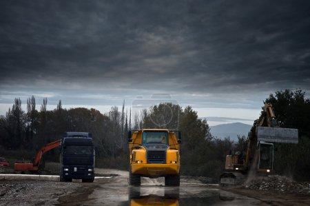 Photo pour Chantier de construction avec camions et pelle - image libre de droit
