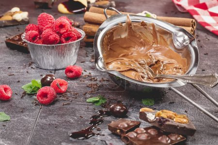 Photo pour Un bol de chocolat fondu avec des framboises pour tremper. Préparer la nourriture. Concept de cuisine. Fait avec un filtre rétro vintage. Macro, focus sélectif - image libre de droit