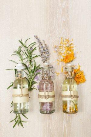 Photo pour Rangée d'huiles essentielles en bouteilles de verre, romarin, lavande et calendula, sur la planche de bois . - image libre de droit