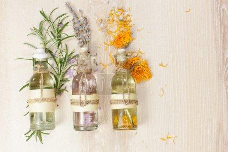 Photo pour Ligne des huiles essentielles dans des bouteilles en verre, romarin, lavande et calendula, sur la planche en bois. - image libre de droit