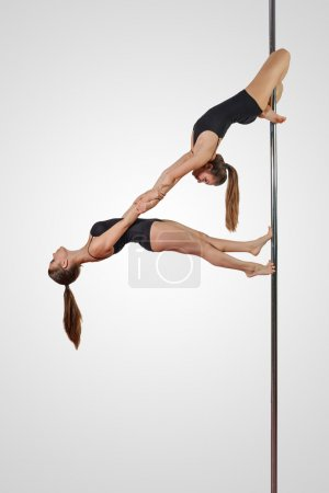 Photo for Two girls in acrobatic position on a pole - Royalty Free Image