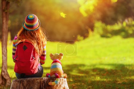 Photo for Young redhead girl sitting on stump with her alive toy cat  and dreaming - Royalty Free Image