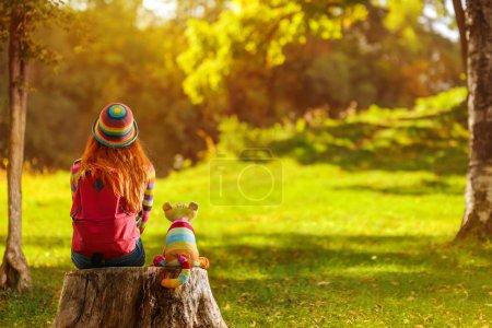 Photo pour Jeune fille rousse assise sur moignon avec son chat jouet vivant et rêvant - image libre de droit