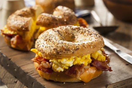 Photo pour Petit déjeuner Sandwich copieux sur un bagel avec bacon aux oeufs et fromage - image libre de droit