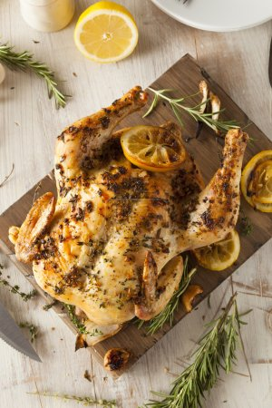 Photo for Homemade Lemon and Herb Whole Chicken on a Cutting Board - Royalty Free Image
