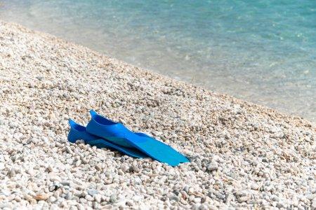 Photo pour Palmes de couleur bleue sur la plage de galets. Equpement de plongée en apnée en mer. - image libre de droit