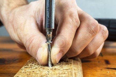 Photo pour Close up of a carpenter screwed a hinge on a wooden plank - image libre de droit