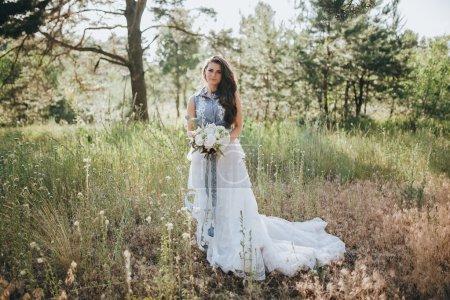 Frau im Brautkleid im Wald