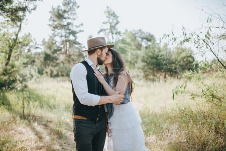 Woman in wedding dress and man in forest