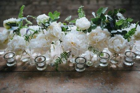 weiße Pfingstrosen in Glasflaschen