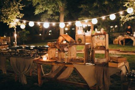 Photo pour Gâteaux et goûters dans des caisses en bois sur la table de buffet décoré - image libre de droit