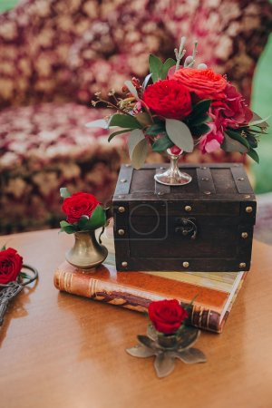 Photo for Vintage Wedding Decor with red flowers on wooden table - Royalty Free Image