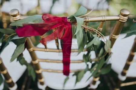 Hochzeit. Zeremonie. Getreide. Kunstwerk. Stühle in Goldfarbe stehen auf dem Rasen im Bereich der Trauung. auf Stühlen Dekoration von Grün und Seidenbändern