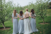 The bride standing and bridesmaids in garden