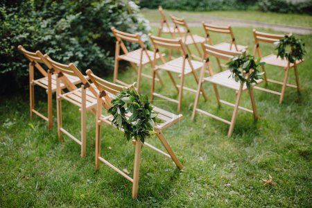 Wooden chairs with a laurel wreath on a green lawn