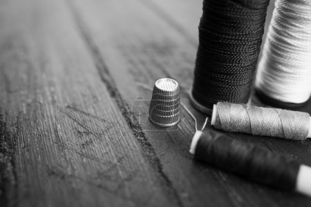 Sewing accessories: bobbins of thread, needle, thimble on wooden table. Black and white photo. Tailoring and sewing concept.
