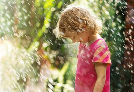 Photo of happy little girl standing under summer rain