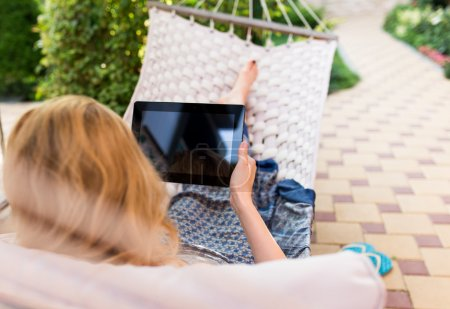 Woman using tablet computer while relaxing in a hammock